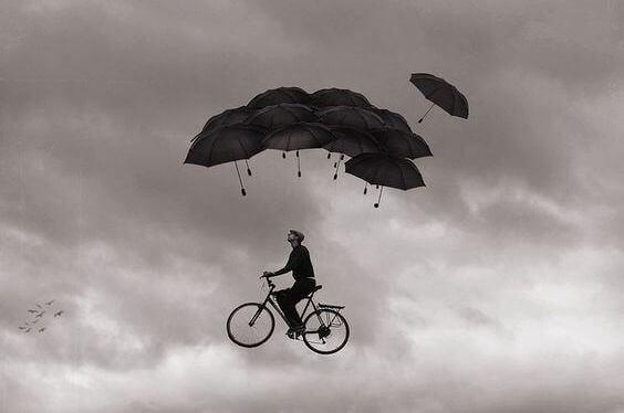 Mann sykler i himmelen under paraplyer