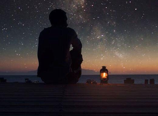 Mann på brygge ser på stjernene
