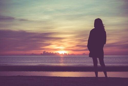 Kvinne ved havet i solnedgang