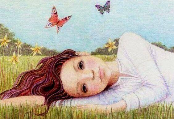 jente ligger i gresset ved sommerfugler
