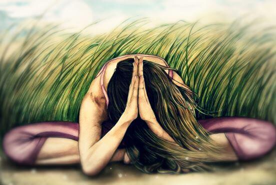 kvinne mediterer i gresset