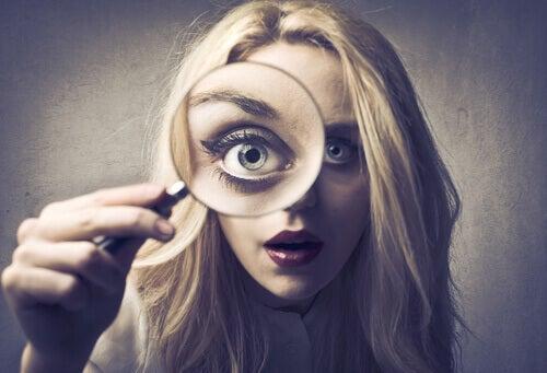 kvinne ser inn i forstorrelsesglass