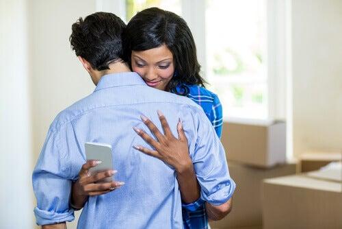 Kvinne er på telefonen mens hun gir klem til en mann