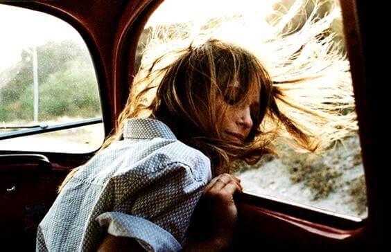 Kvinne stikker hodet ut av bilvindu