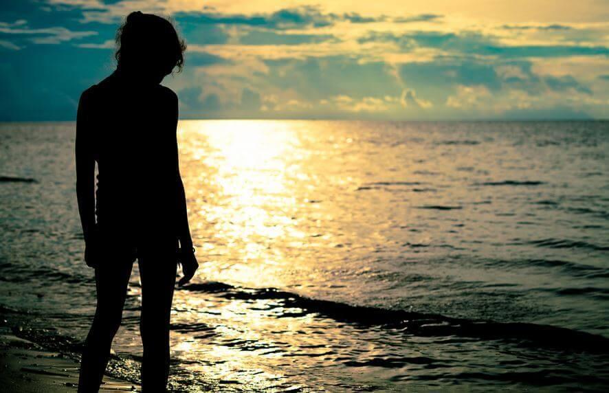 Person ved havet i solnedgangen