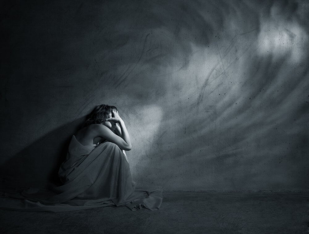 Trist kvinne i mørket