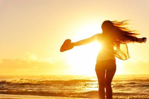 Lykkelig kvinne på stranden i solnedgangen