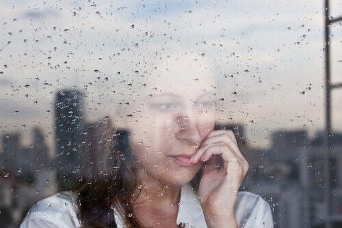 Kvinne ser ut regnfullt vindu
