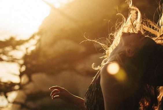 Lykkelig kvinne i solen