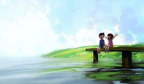 Gutt og jente sitter på brygge