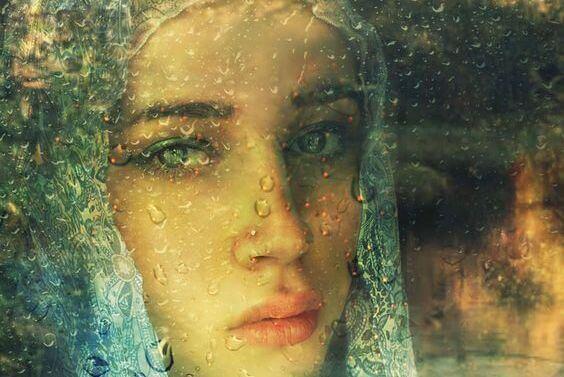 Trist kvinne ved vått vindu