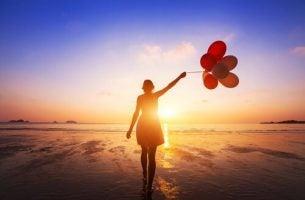 Kvinne med ballonger foran havet