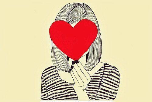 Kvinne holder et hjerte foran ansiktet