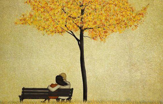 Par på en benk under et tre