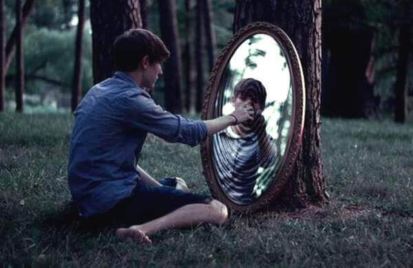 Gutt ser i speil i skogen