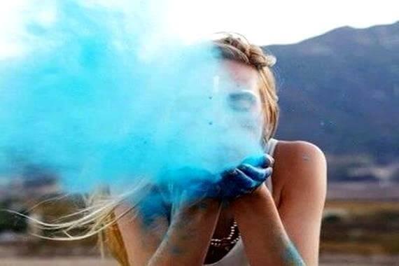Kvinne som har en sunn selvfølelse blåser blått støv