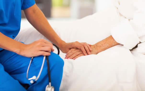 Sykepleier holder pasientens hånd