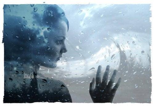 Trist kvinne bak vått vindu