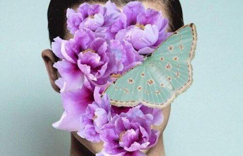 Kvinne med blomst og sommerfugl i ansiktet