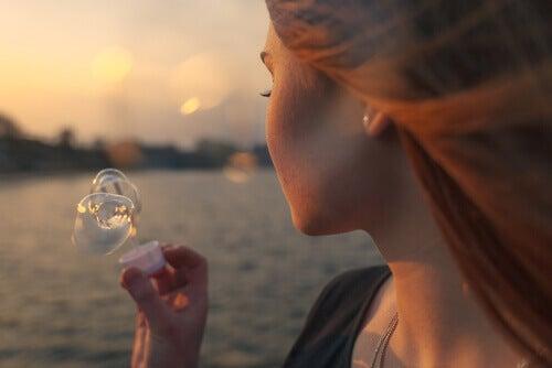 Kvinne blåser bobler ved sjøen