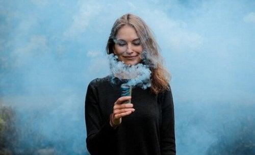 Kvinne smiler, omgitt av røyk