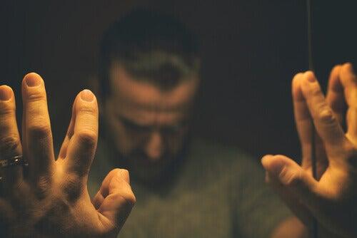 Mann i dårlig humør lener seg mot speil
