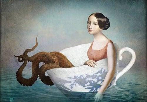 Kvinne med blekksprutben i en kopp på havet