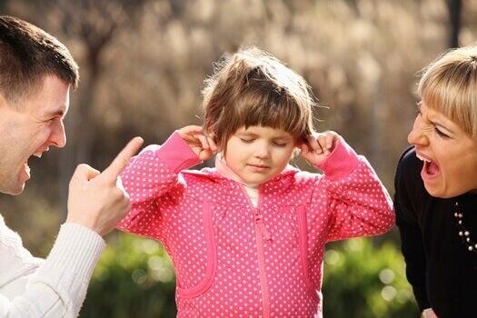 En liten jente som er fanget mellom foreldre som krangler