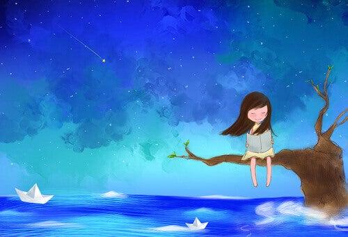 Liten jente sitter på en gren over havet og leser