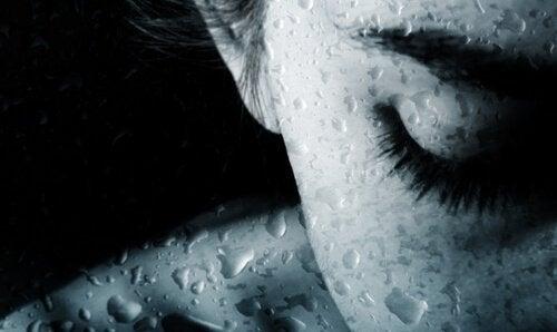 Kvinne gråter bak vått glass