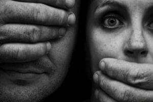 Mann holder hendene for sine øyne og kvinnes munn