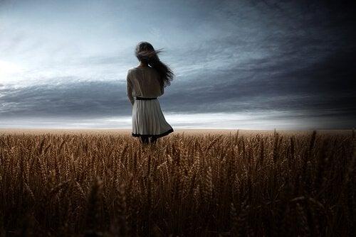 En jente i en hveteåker som tenker på muligheter