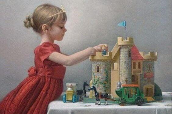 En liten jente bærer en tiara og leker med et slott