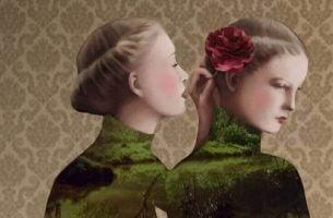 Kvinne hvisker i annen kvinnes øre