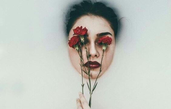 Kvinne med blomst foran ansiktet