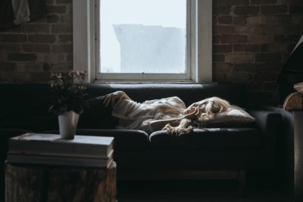 Kvinne sover på sofaen