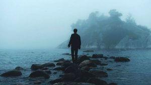 en ensom mann i et regnfullt hav