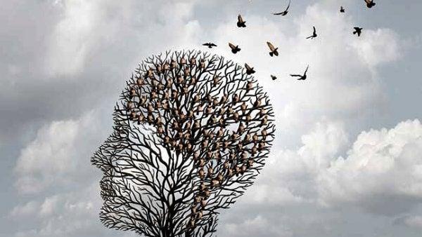 profil av et ansikt laget av fugler i et tre