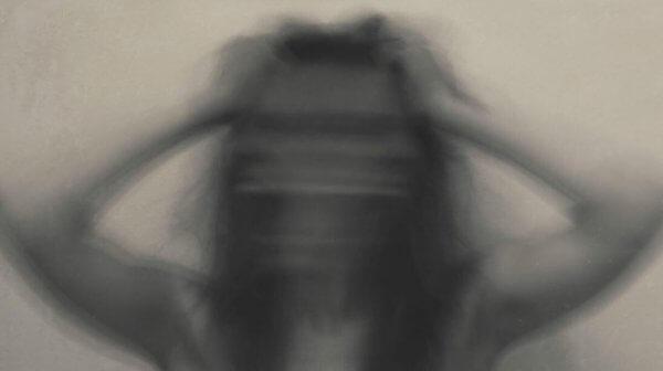 en uklar kvinne med hendene til hodet i angst