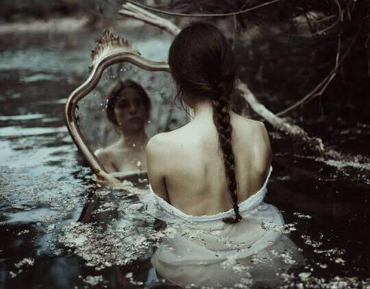 Kvinne i vann ser i speil