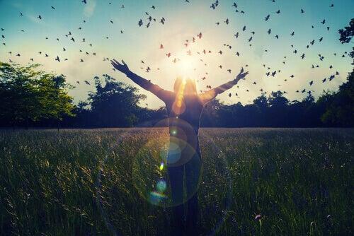 Jente i en eng, omgitt av fugler