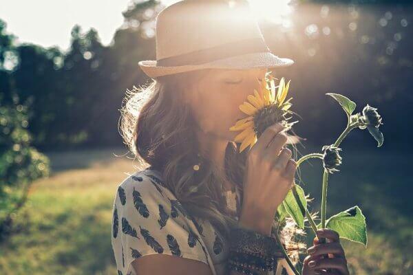 Kvinne lukter på blomst og praktiserer positiv tenkning