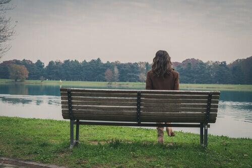 Kvinne sitter på en benk i parken og dveler ved fremtiden