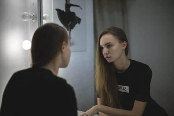 En trist kvinne ser i speilet