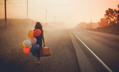 Kvinne med ballonger og en koffert