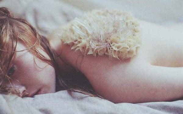 Trist kvinne ligger i sengen