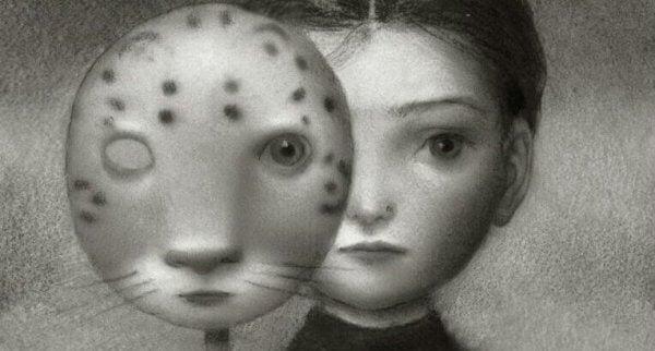 En liten jente som holder en tigermaske foran ansiktet