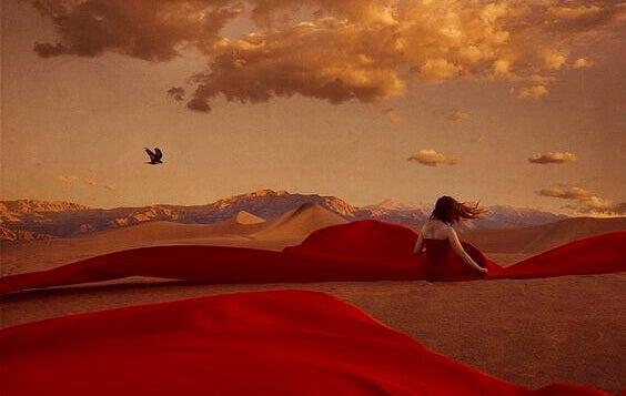 Kvinne med rød kjole i ørkenen