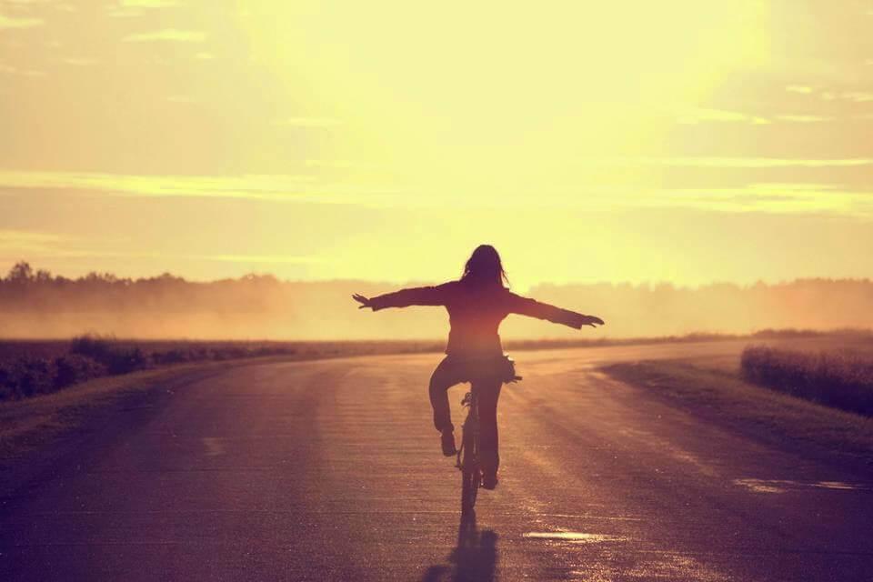 Kvinne sykler i solnedgang