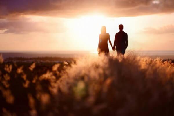 Par i en eng holder hender i solnedgangen
